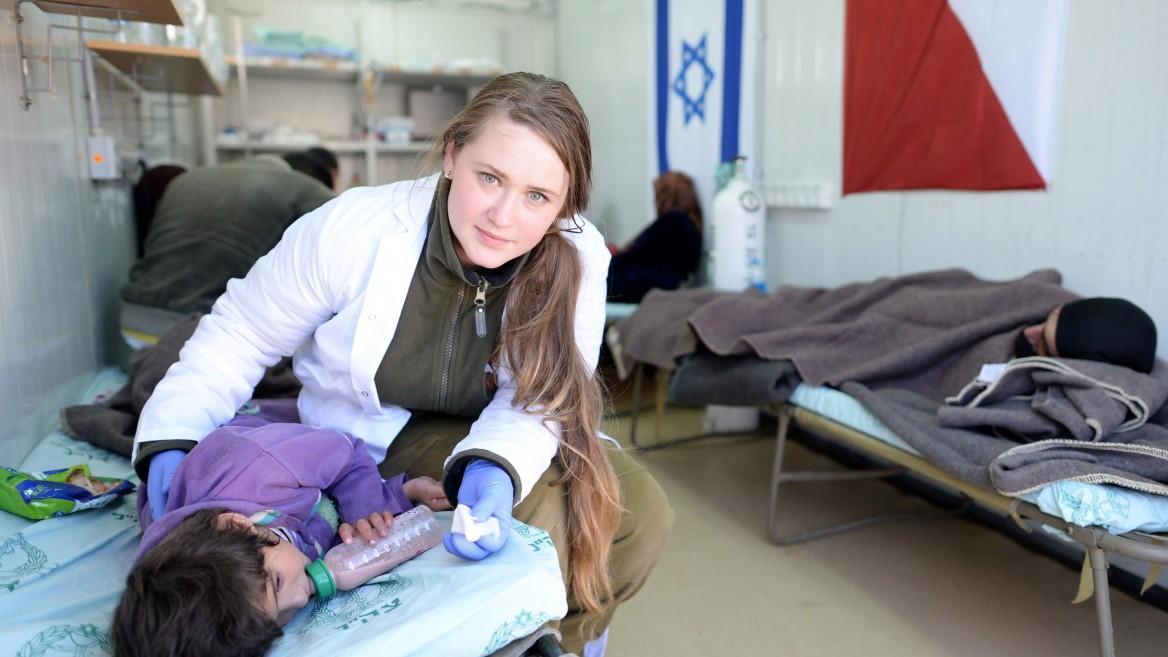 """חובשת ישראלית נותנת סיוע לילדה סורית בבי""""ח סדה בצפון ישראל"""